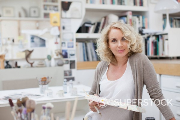 Stock Photo: 1775R-35482 Woman holding paintbrush and palette in art studio