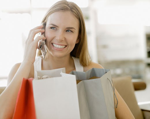 Woman talking on cell phone with shopping bags smiling : Stock Photo