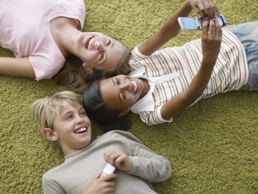 Stock Photo: 1775R-3784 Three young kids two with cellular phones