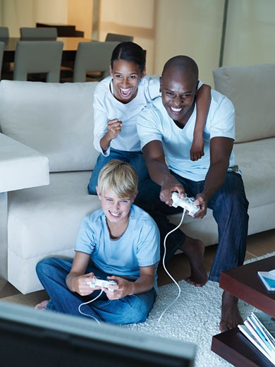 Man and two young kids playing a video game : Stock Photo