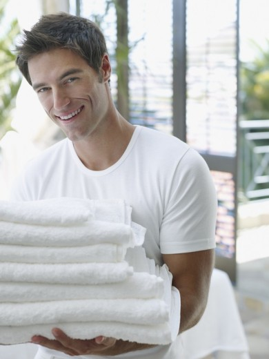 Man with a pile of towels in his arms : Stock Photo