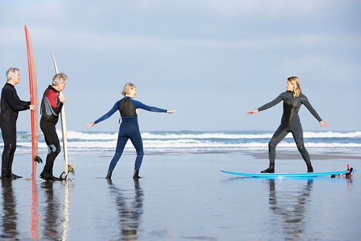 Stock Photo: 1775R-3928 Four adults on the beach with surfboards
