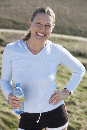 Stock Photo: 1775R-3982 mature woman with a bottle of water resting after a jog