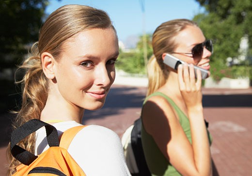 Two young girls outdoors one is on her cellular phone : Stock Photo