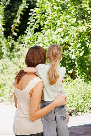 A mother and daughter embracing looking at some wildlife : Stock Photo