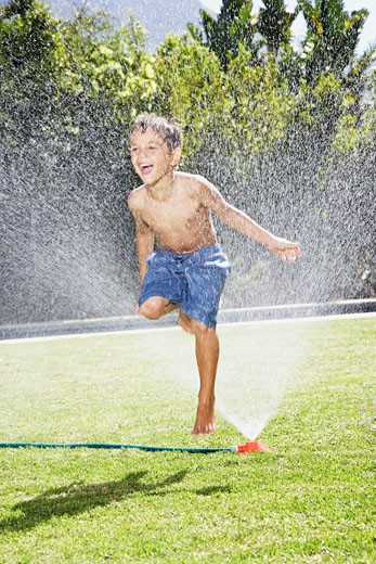 A young boy playing in a sprinkler : Stock Photo