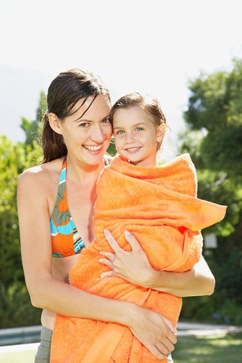 A mother holding her daughter in a towel after a swim : Stock Photo