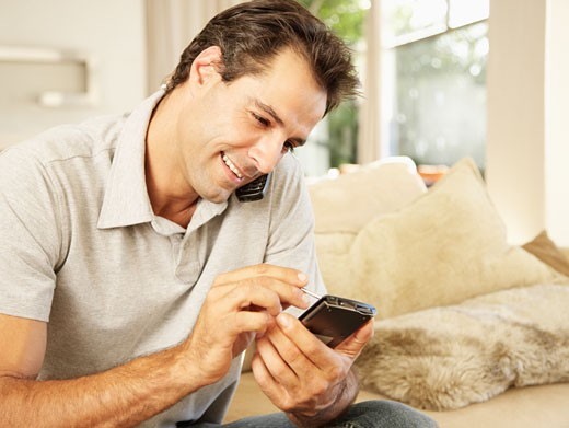 Man on a cellular using a personal digital assistant : Stock Photo