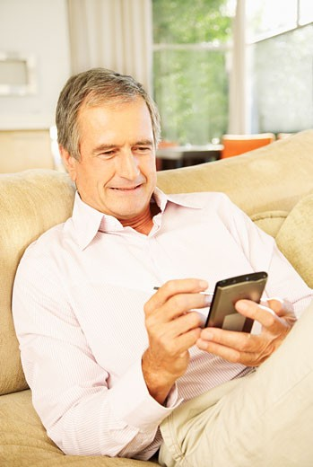 Stock Photo: 1775R-4506 senior man using a personal digital assistant