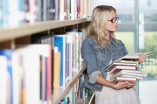 Stock Photo: 1775R-4645 Teenage girl in library at school with books