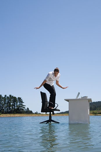 A woman on her office chair on top of water : Stock Photo