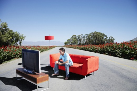 A man watching television on a couch in the road : Stock Photo