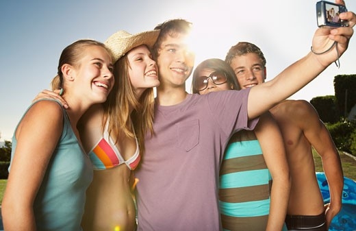Stock Photo: 1775R-5166 Friends hanging out by a pool taking pictures