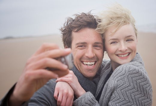 Stock Photo: 1775R-5486 A couple taking pictures at the beach