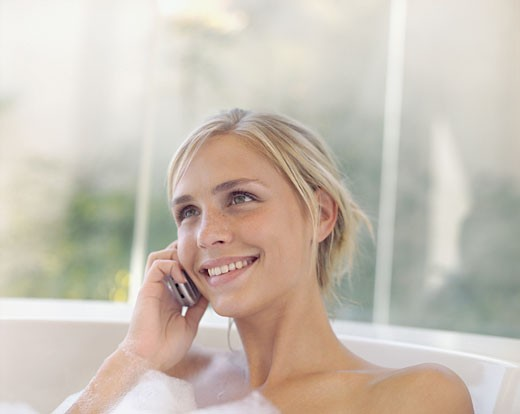 Stock Photo: 1775R-5627 A woman in a bathtub on her cellular phone