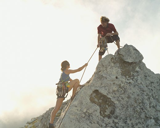 Stock Photo: 1775R-5972 A man helping a woman climber to the top of the mountain