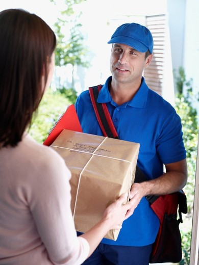 Male delivery person giving package to woman : Stock Photo