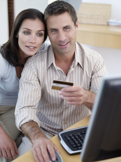 Man with credit card and computer with woman : Stock Photo