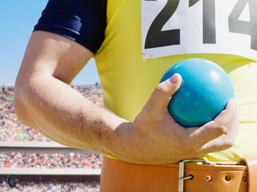 Athlete holding shot-put ball in an arena : Stock Photo