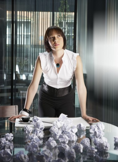 Businesswoman standing with crumpled papers in an office : Stock Photo
