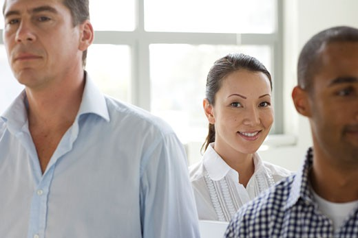 Stock Photo: 1775R-6501 Businesswoman standing with two coworkers smiling
