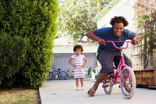 Stock Photo: 1775R-6555 Father riding daughter´s bicycle in driveway
