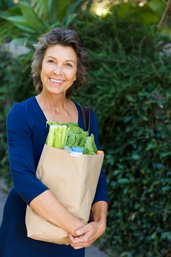 Woman carrying groceries in brown bag : Stock Photo