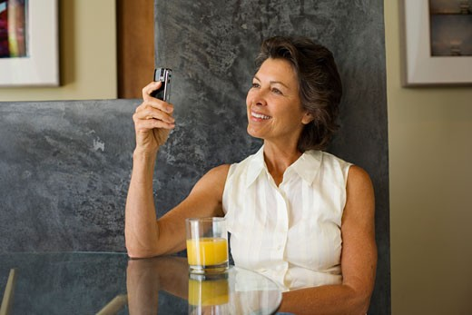 Stock Photo: 1775R-6738 Woman sitting at a table with orange juice and a mobile phone