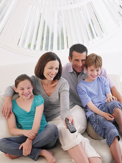 Stock Photo: 1775R-6814 Couple with young boy and girl on sofa with television remote