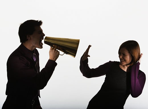 Businessman with bullhorn shouting at woman : Stock Photo