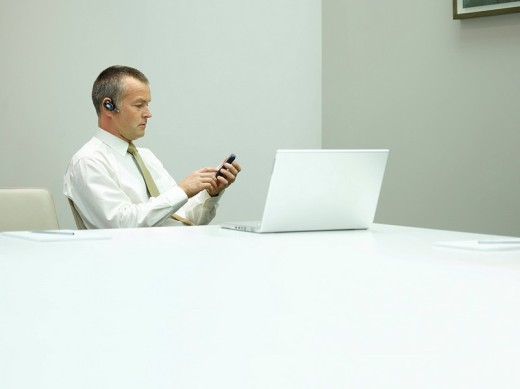 Businessman in office on mobile phone with laptop on table : Stock Photo