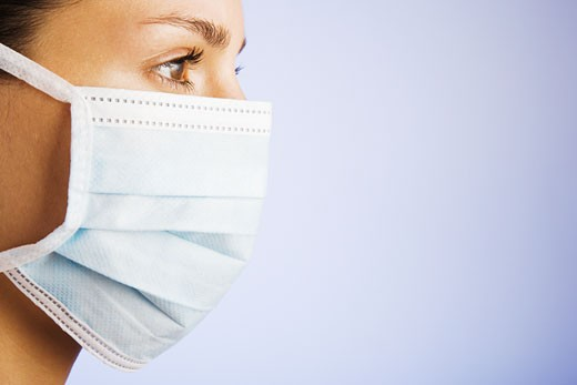 Woman wearing a surgical mask : Stock Photo