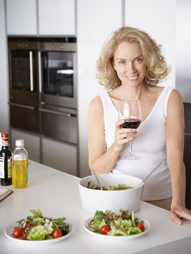Woman standing with wine by bowls of salad : Stock Photo