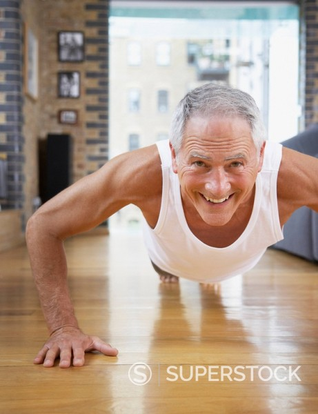 Stock Photo: 1775R-7305 Man doing pushups in living room