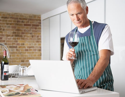 Man looking at laptop with glass of wine : Stock Photo