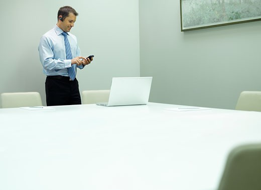 Man with mobile phone and laptop in an office : Stock Photo