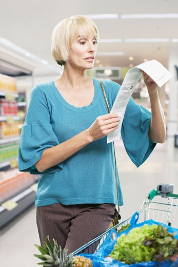 Woman looking at bill in grocery store : Stock Photo