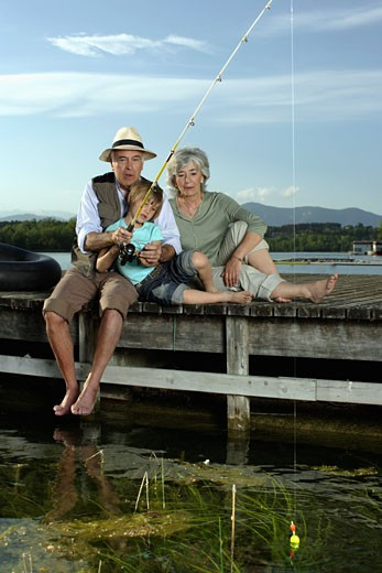 Couple fishing with young boy on dock : Stock Photo