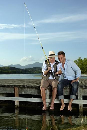 Stock Photo: 1775R-7837 Two men fishing on dock