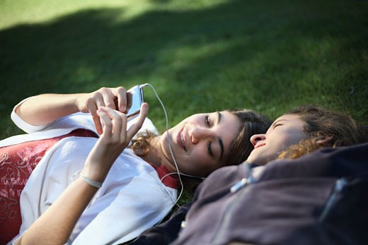 Two girls lying in grass with an MP3 Player : Stock Photo
