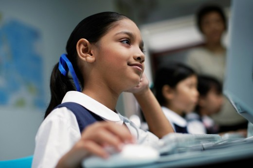Stock Photo: 1775R-8185 Girl at computer in classroom with other students in background