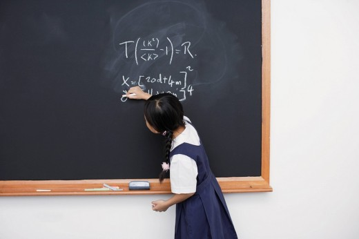 Girl writing on blackboard in classroom : Stock Photo