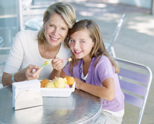 Stock Photo: 1775R-8446 Woman and young girl on outdoor patio eating ice cream