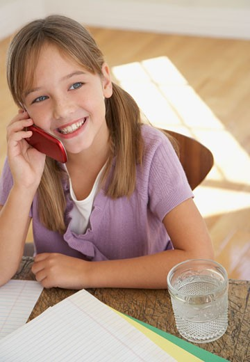 Young girl with mobile phone and homework at kitchen table : Stock Photo