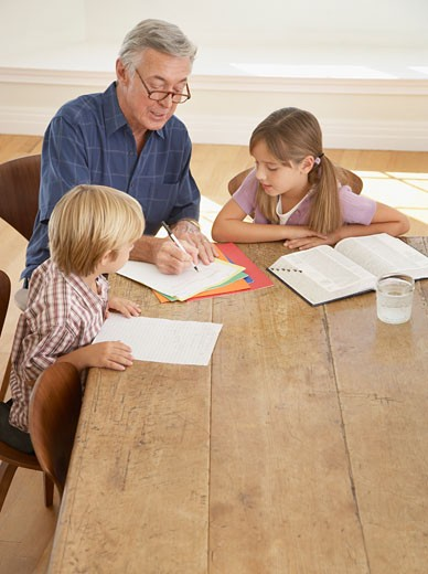 Stock Photo: 1775R-8474 Man helping two kids with homework at kitchen table
