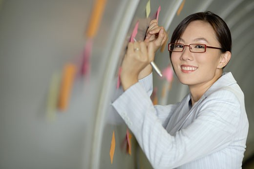 Stock Photo: 1775R-9104 Businesswoman in corridor sticking post-its to a wall