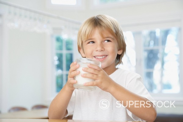 Young boy in kitchen drinking glass of milk : Stock Photo