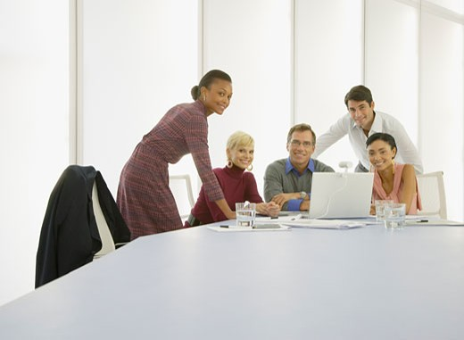 Five businesspeople in a boardroom with a laptop : Stock Photo