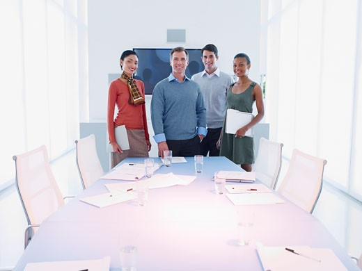 Stock Photo: 1775R-9277 Four businesspeople in a boardroom looking at camera