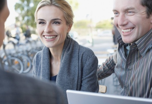 Couple and man on outdoor patio with laptop : Stock Photo